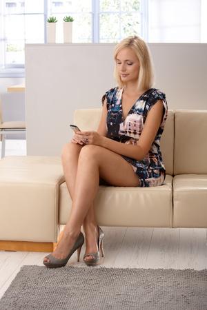 mujeres sentadas: Atractiva mujer rubia en mini vestido con tel�fono m�vil, mensajes de texto, sentado en el sof�, sonriente.