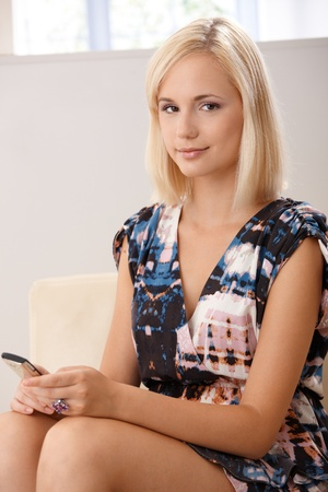 Portrait of young attractive blonde woman with mobile phone handheld, smiling at camera. photo