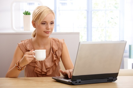 Portrait of young businesswoman on coffee break, using laptop computer at desk. photo