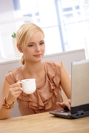 vertical image: Young blond woman having coffee, holding coffee cup, using laptop computer, smiling. Stock Photo