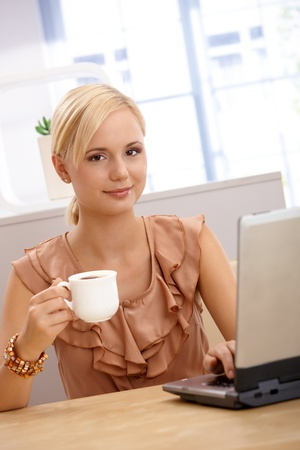 Portrait of young attractive blonde office worker woman on coffee break, using computer. photo