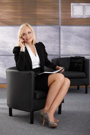 mujeres sentadas: Empresaria sonriendo sentado en el sill�n, hablando por tel�fono m�vil, sonriente, con un organizador personal.