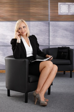 Smiling businesswoman sitting in armchair, talking on mobile phone, smiling, using personal organizer. photo