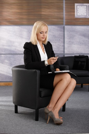 Businesswoman waiting in office lobby armchair, using mobile phone texting, holding personal calendar. photo