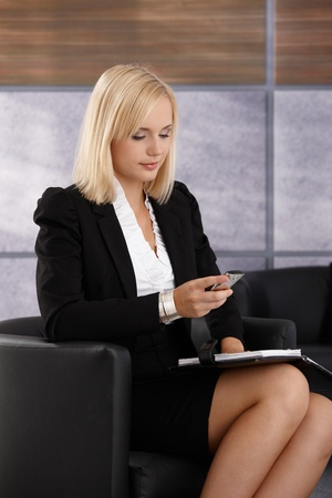 checking: Smart young businesswoman checking mobile phone, holding personal calendar, sitting in office armchair.