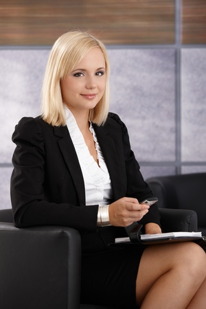 Portrait of confident smiling young businesswoman sitting with cellphone and personal organizer handheld, looking at camera. photo