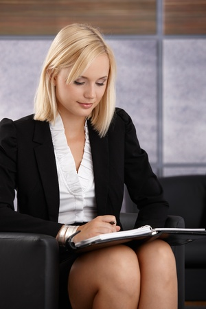 Young businesswoman checking personal calendar while sitting in office lobby. photo