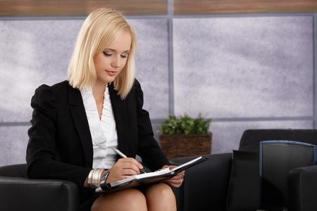 taking note: Attraente imprenditrice seduto in ufficio elegante poltrona, occupata note prendendo in calendario personale.
