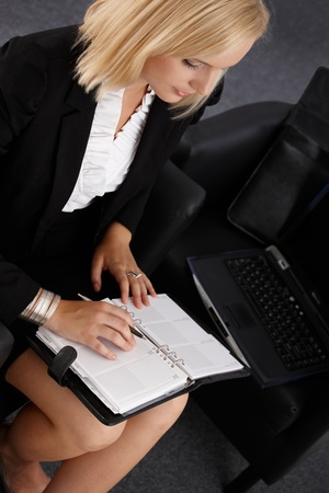 Young businesswoman using personal organizer, taking notes, elevated view. photo