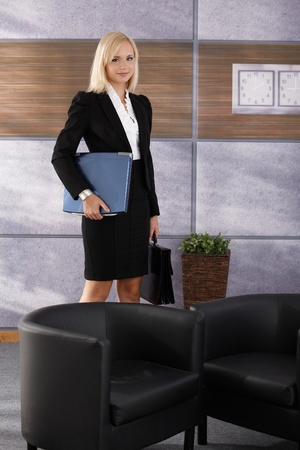 Portrait of attractive businesswoman standing in office lobby with laptop and briefcase, smiling at camera. photo