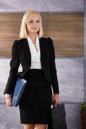 Portrait of smiling young businesswoman standing in office with laptop computer and briefcase handheld. photo