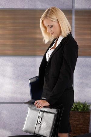 Attractive businesswoman standing in office, holding laptop computer and closing business briefcase. photo