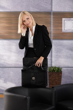 Businesswoman standing in office lobby, on mobile phone call, opening briefcase, taking out personal organizer, smiling. photo