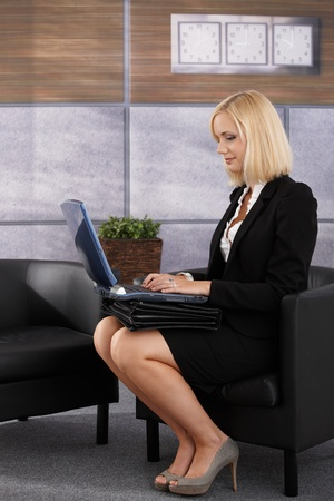 Pretty businesswoman sitting in office lobby, working on laptop computer in armchair, smiling. photo
