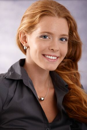 Closeup portrait of beautiful elegant woman with long red curly hair smiling at camera happily. photo