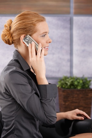 Businesswoman sitting in office lobby on mobile phone call, smiling, side view portrait. photo