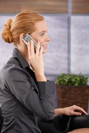 persona llamando: Mujer de negocios sentado en el vestíbulo de la oficina llamada de teléfono móvil, sonriente, retrato vista lateral.