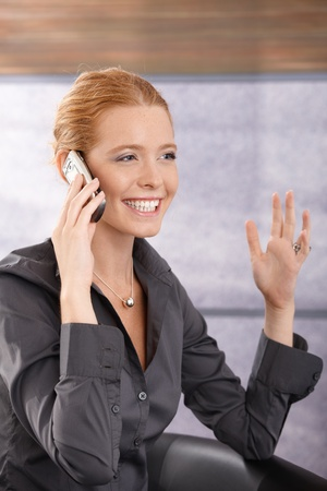 Happy young businesswoman laughing on phone call, gesturing with hand, sitting in office lobby. Stock Photo - 11157733