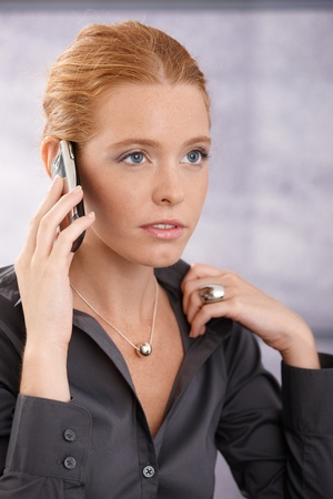Closeup portrait of young businesswoman concentrating on mobile phone call. Stock Photo - 11157753