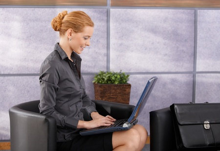 beautiful redhead: Portrait of smiling businesswoman working on laptop computer in office lobby, side view.