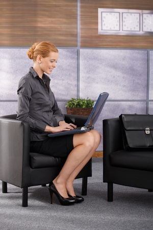 seated: Happy businesswoman sitting in office armchair working on laptop computer, smiling. Full length side view portrait. Stock Photo