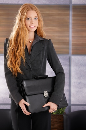 Portrait of pretty young businesswoman standing in office, holding briefcase, smiling at camera. photo