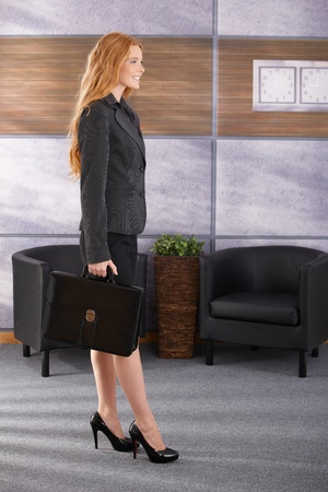 Smiling smart businesswoman arriving to office with briefcase. photo