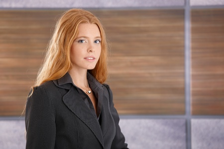 Portrait of attractive redhead businesswoman smiling at camera. photo