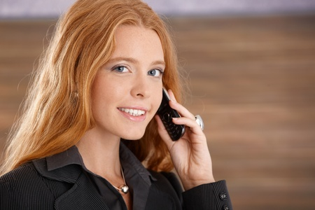 Closeup facial portrait of happy businesswoman on mobile phone call, looking at camera. photo