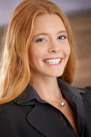 Closeup portrait of happy laughing young businesswoman smiling at camera. photo