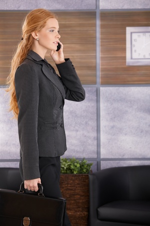 Businesswoman busy speaking on mobile phone arriving to office with briefcase handheld. photo