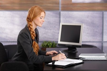 braided hair: Young businesswoman working at desk in office, taking notes into personal calendar, smiling.
