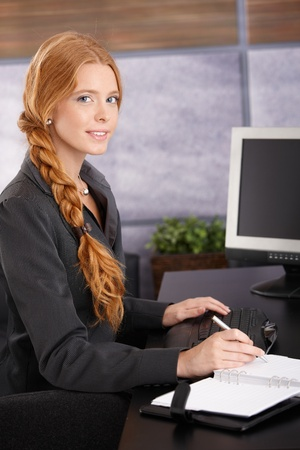 Portrait de femme d'affaires attractif rousse au travail, assis à son bureau en utilisant un organiseur personnel, souriant à la caméra.