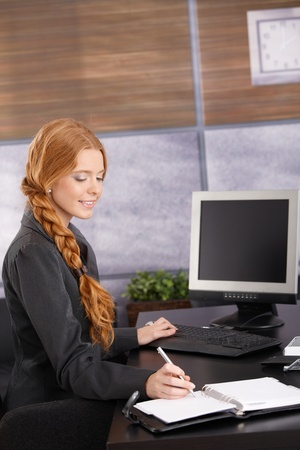 indoor photo: Happy businesswoman working at desk, using computer and taking notes, smiling.