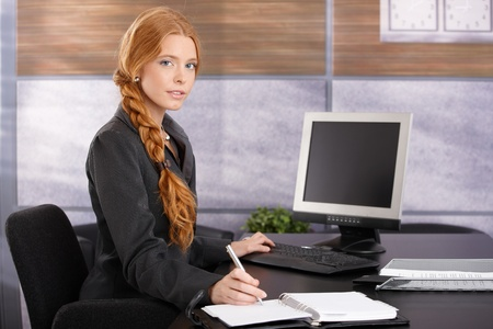 braided hair: Portrait of working businesswoman sitting at office desk, looking at camera confidently.