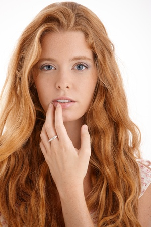 Pretty redhead portrait, closeup face and hand, touching lips, looking at camera, beautiful long red curly hair. photo