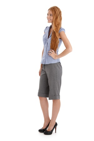 full size: Portrait of pretty redhead posing in studio, full length, cutout on white. Stock Photo