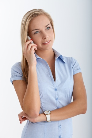 Smiling blonde teen concentrating on cellphone call with arms folded.