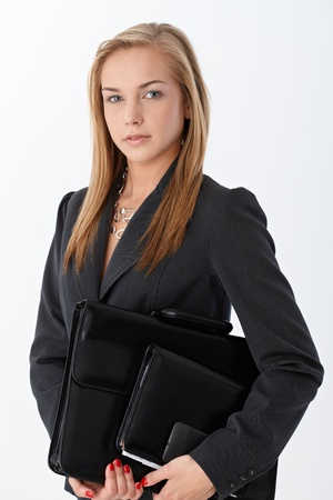 Businesswoman with accessories, briefcase, personal organizer and mobile phone handheld, looking confidently at camera. photo