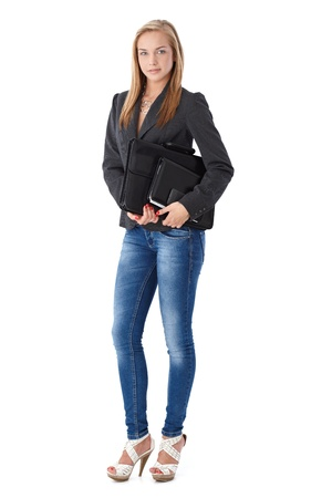 formal attire: Casual business portrait of young businesswoman with briefcase and organizer, posing in studio, full length. Stock Photo