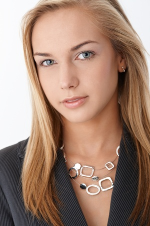 Closeup facial portrait of young smart businesswoman smiling at camera confidently. photo