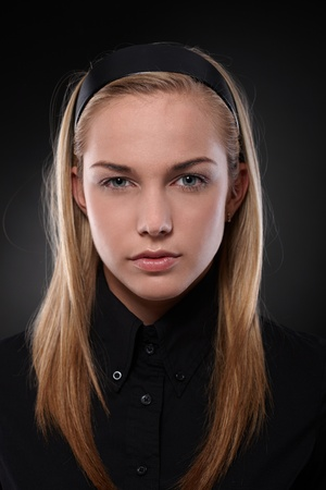 offish: Closeup portrait of severe teenage girl wearing black, looking at camera.