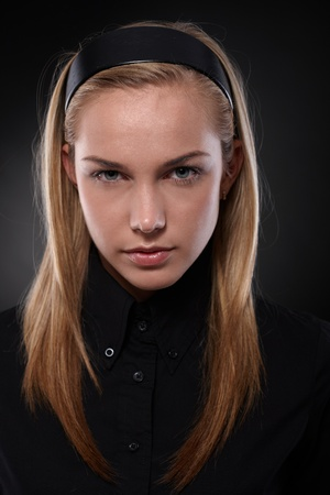 dark blond: Unsmiling teenager wearing black looking at camera.