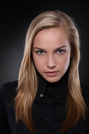 serious woman: Studio portrait of unsmiling, blonde teenager in black, black background .