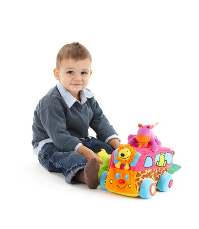 Baby boy sitting with colorful toys, smiling at camera. photo