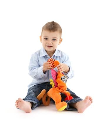 Niño pequeño se sienta feliz, jugando con los juguetes del bebé, sonriendo.