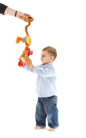 Baby boy standing, getting colorful toy from mother hand, cutout on white. photo