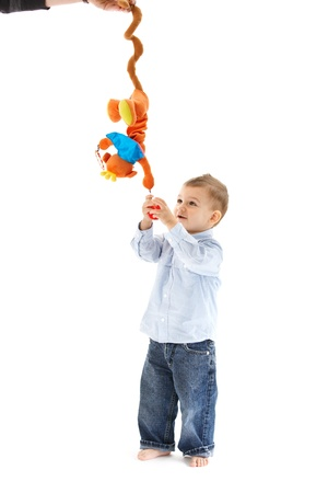 Smiling baby boy with standing with colorful developmental toy. photo