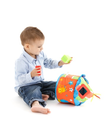 Little kid playing with developmental soft toy. photo