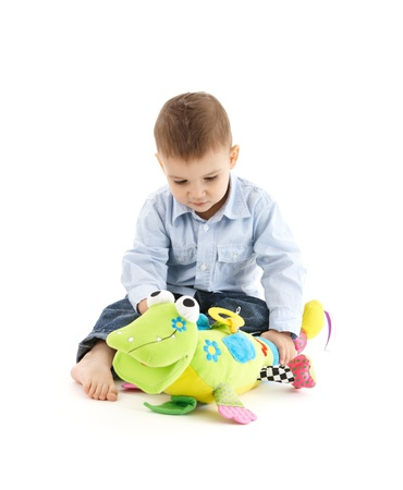 boys toys: Adorable toddler boy playing with cute soft toy, cutout on white.